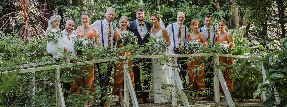 Wedding Party Posing for Wedding Photos on Leafy Bridge at Tabula Rasa Wedding and Event Centre