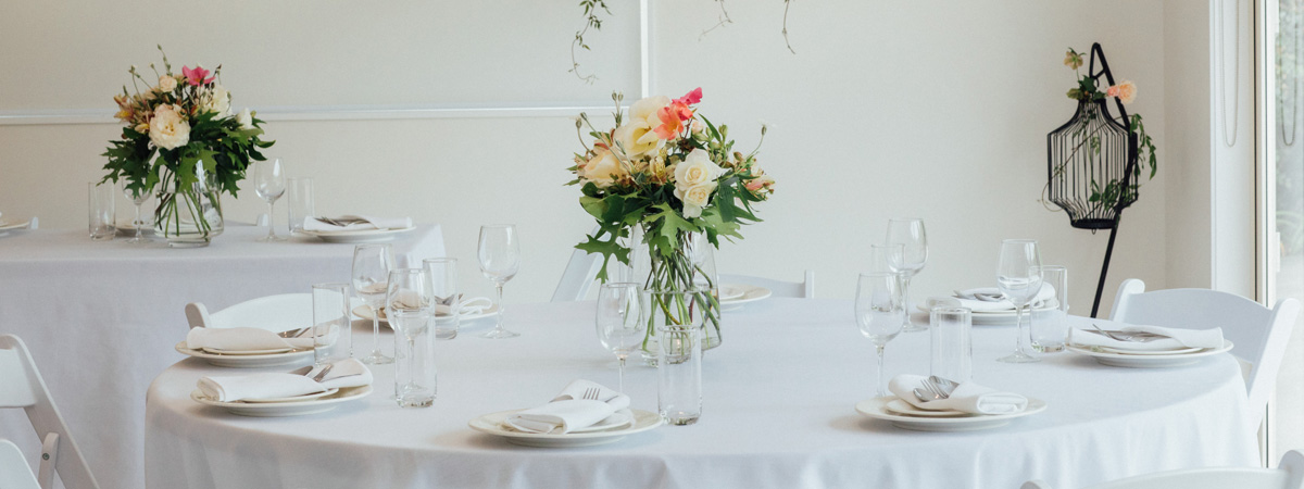 WhiteCircular Table Set for A Wedding With Cutlery, Wine Glasses and Flowers