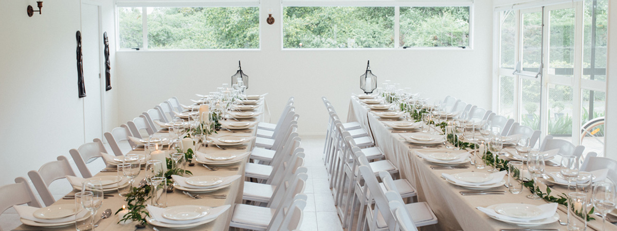 Two Long Wooden Tables Side By Side Set With Plates And Wine Glasses.